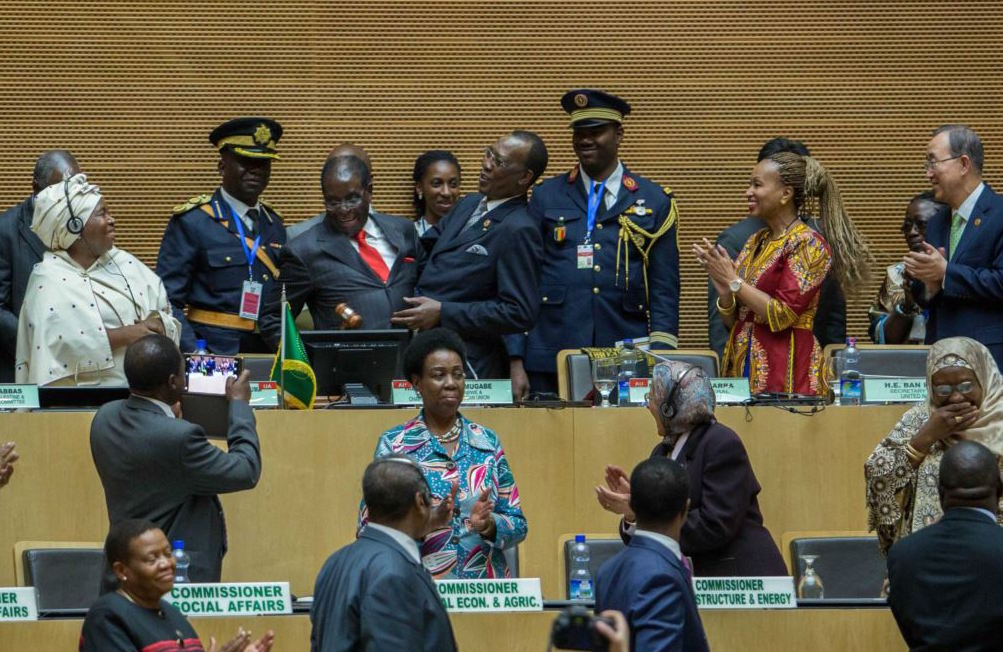 African Union chairman Chadian President Idriss Deby, fourth left, receives the instruments of office from his predecessor Zimbabwean President, Robert Mugabe, as AU Commission Chairperson Nkosazana Dlamini Zuma, left, African Union chairman Chadian President Idriss Deby, fourth left, receives the instruments of office from his predecessor Zimbabwean President, Robert Mugabe, third left in red tie, as African Union Commission Chairperson Nkosazana Dlamini Zuma, left, and UN Secretary General , Ban Ki-moon, right, watches, in Addis Ababa.